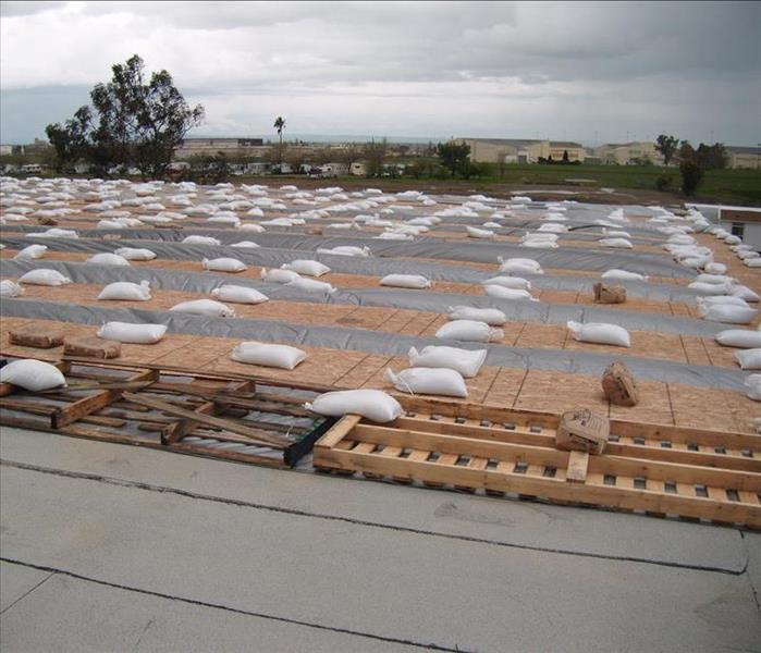 Commercial roof tarping during a wind and rain storm